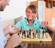 Hijo del hombre y del adolescente que juega a ajedrez Fotos de archivo