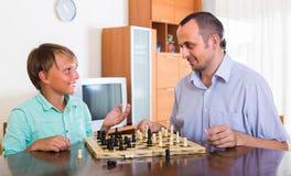 Hijo del hombre y del adolescente que juega a ajedrez Imagen de archivo libre de regalías