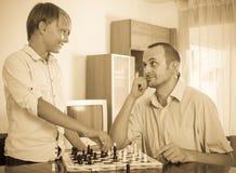 Hijo del hombre y del adolescente que juega a ajedrez Fotos de archivo libres de regalías