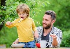Hijo del padre comer la comida y divertirse h?bitos alimentarios Ni?o peque?o con el pap? que come el fondo de la naturaleza de l fotos de archivo