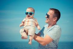 Hijo del padre y del bebé que juega en la playa en el tiempo del día Imagen de archivo