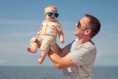 Hijo del padre y del bebé que juega en la playa en el tiempo del día Imágenes de archivo libres de regalías