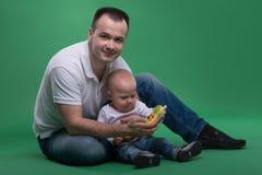 Hijo del padre y del niño que juega con el teléfono celular del juguete Fotos de archivo