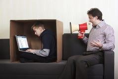Hijo del tween que se sienta en una caja de cartón con un ordenador portátil mientras que su padre grita en él a través de un meg Imagen de archivo