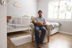 Hijo durmiente del bebé de los controles de la silla de Sitting In Nursery del padre imagenes de archivo