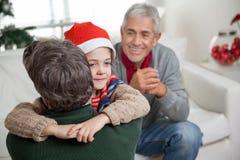 Hijo en Santa Hat Embracing Father Imagenes de archivo