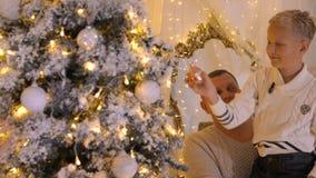 Hijo feliz en las manos del padre que adorna el árbol de navidad por el juguete en sitio acogedor almacen de metraje de vídeo