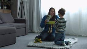 Hijo lindo del liitle que da un regalo a su madre feliz almacen de video