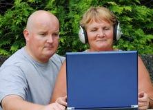 Hijo mayor de la madre en la computadora portátil afuera Fotos de archivo libres de regalías