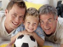 Hijo, padre y abuelo sonrientes en suelo imágenes de archivo libres de regalías