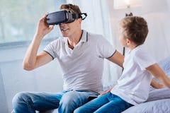 hijo Pre-adolescente que mira sus auriculares de la prueba VR del padre Imágenes de archivo libres de regalías