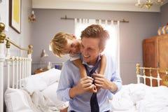 Hijo que abraza al padre As He Gets vestido para el trabajo fotos de archivo