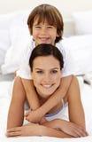 Hijo que abraza a su madre en cama Foto de archivo libre de regalías