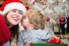 Hijo que besa a su madre el mañana de la Navidad Fotografía de archivo libre de regalías