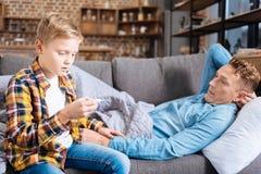 Hijo que cuida que comprueba temperatura de su padre enfermo Fotos de archivo libres de regalías