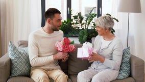 Hijo que da el presente y las flores a la madre mayor almacen de metraje de vídeo