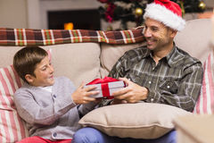Hijo que da a padre un regalo de la Navidad en el sofá Foto de archivo libre de regalías