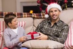 Hijo que da a padre un regalo de la Navidad en el sofá Fotografía de archivo
