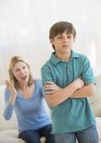 Hijo que ignora a la madre enojada en casa Foto de archivo