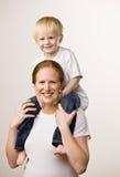 Hijo que lleva de la madre feliz en sus hombros Fotografía de archivo