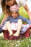 Hijo que lleva de la madre que se sienta en cesta de lavadero Imágenes de archivo libres de regalías