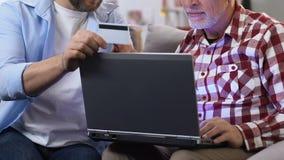 Hijo que muestra la tarjeta de crédito al padre y que explica cómo a la actividad bancaria en el ordenador portátil almacen de metraje de vídeo