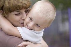 Hijo que se besa y de abarcamiento de la mujer en parque Fotografía de archivo libre de regalías