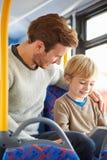 Hijo que usa la tableta de Digitaces en viaje del autobús con el padre Imagenes de archivo
