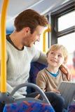 Hijo que usa la tableta de Digitaces en viaje del autobús con el padre Foto de archivo libre de regalías