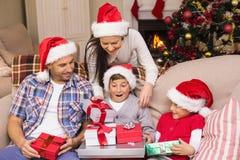 Hijo sorprendido que abre sus regalos Fotografía de archivo
