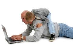 Hijo y computadora portátil del padre Imagen de archivo libre de regalías