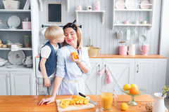 Hijo y madre joven en la cocina que comen el desayuno fotos de archivo