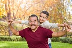 Hijo y padre caucásicos hispánicos Having Fun At de la raza mixta el parque foto de archivo