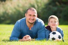 Hijo y padre con la bola del fútbol Fotos de archivo