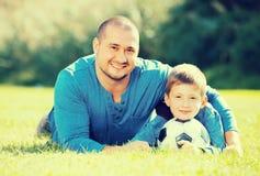 Hijo y padre con la bola del fútbol Foto de archivo