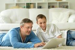 Hijo y padre que usa el ordenador portátil Fotos de archivo libres de regalías