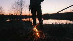 Hijo y papá por el fuego, pies de primer familia que acampa en riverbank en la noche metrajes