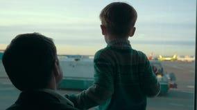 Hijo y papá que miran área del aeropuerto con almacen de metraje de vídeo