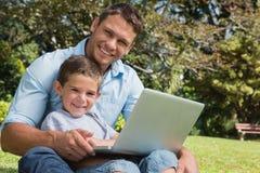 Hijo y papá sonrientes con un ordenador portátil Fotos de archivo