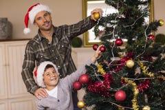 Hijo y papá sonrientes que adornan el árbol de navidad Imagenes de archivo