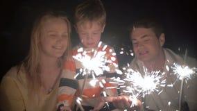 Hijo y sus padres que cogen chispas de un Bengale almacen de video