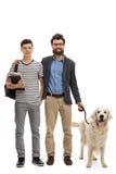 Hijo y un padre con un perro Fotos de archivo libres de regalías