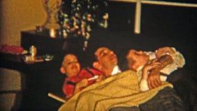 1954: Hijos que abrazan en el sofá con el padre NEWARK, NEW JERSEY almacen de video
