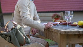After the hike couple comes to the local restoration. Close up RAW footage of a man coming to seat behind the wooden eating table in the garden of a local stock video footage