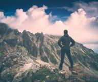 Hike enjoy the blue sky. Instagram stylisation. Hiker stays on a rocky ridge and enjoy blue sky above the mountain valley. Caucasian, Georgia, Swaneti region Stock Photography