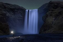 A hike standing below Skogafoss waterfall at night. A man exploring skogafoss at night with green glow and stars above Skogafoss waterfall in south Iceland stock image