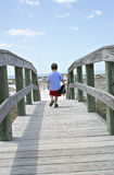 Hike to the beach. A little boy hiking over the boardwalk to the beach stock images