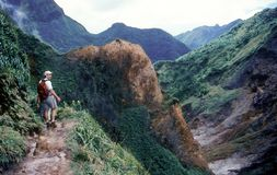 On the Hike to the Boiling Lake in Dominica. A hiker treks along a rim above the `Valley of Desolation` on the trail through Morne Trois Pitons National Park on stock photography