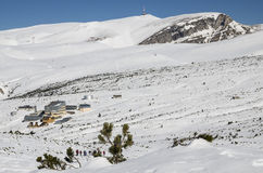 A hike in winter, towards the chalet. People going on a winter hike on a snowy mountain plateau towards the Piatra Arsa Chalet, Bucegi Mountains, Romania Stock Photos