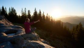 Hiker женщины сидя на валуне в горах на заходе солнца стоковое изображение